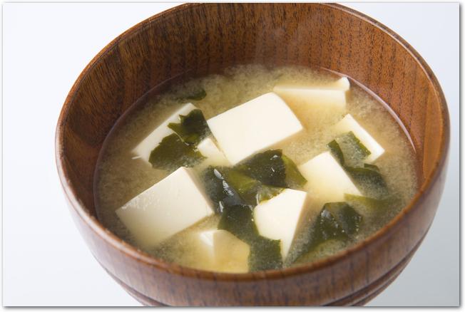 木のお汁椀に入った豆腐とわかめの味噌汁