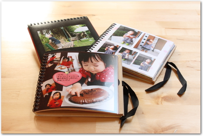 テーブルに置かれた小さい女の子のフォトブック3冊