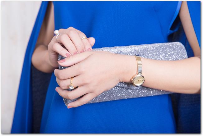 シルバーのクラッチバッグを持つパーティードレスを着た女性の手元