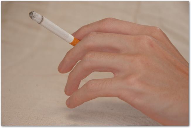 火のついたタバコを持つ手と煙