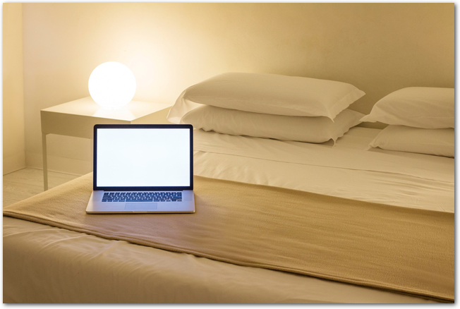 ホテルのベッドの上に置かれたノートパソコン