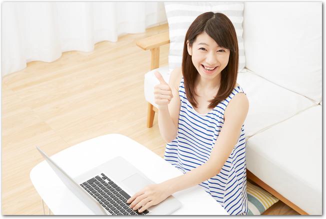 リビングでノートパソコンを操作する笑顔の女性