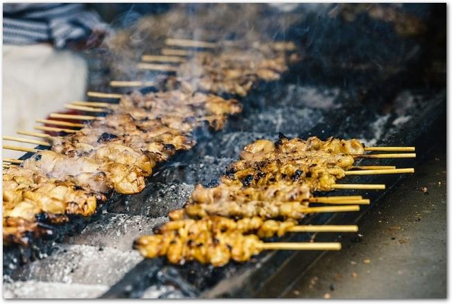 屋台で焼かれているたくさんの焼き鳥串の様子