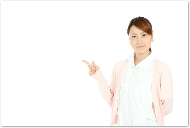 指さしをする白衣を着た女性の看護師