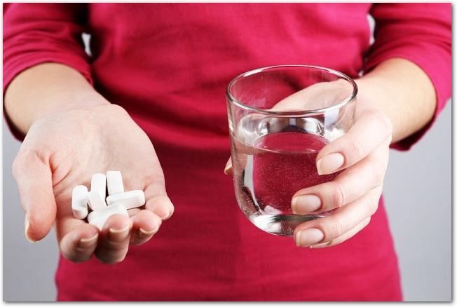 錠剤とグラスに入った水を持つ両手