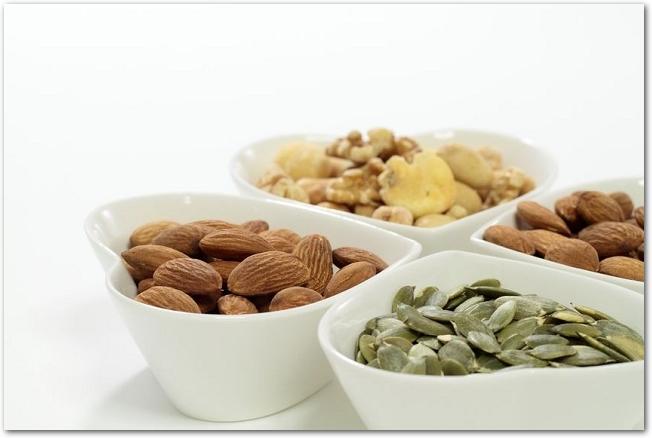 ハートの器に盛られたカボチャの種やアーモンドなどのナッツ