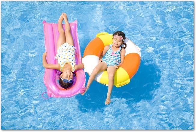 浮き輪に乗ってプールに浮かぶ2人の女の子