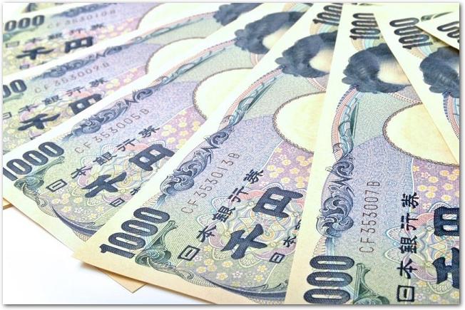 白背景に置かれた数枚の千円札