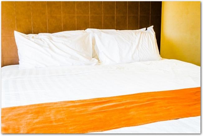 オレンジ色の装飾が入ったホテルのダブルベッド