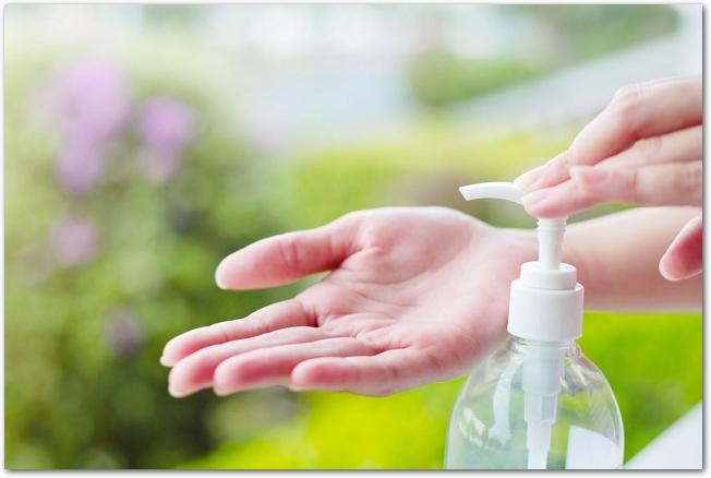 消毒用エタノールで手を綺麗にしている女性の手元