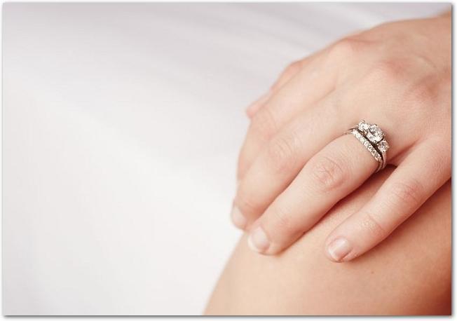 エンゲージリングとマリッジリングを重ねづけしている女性の左手