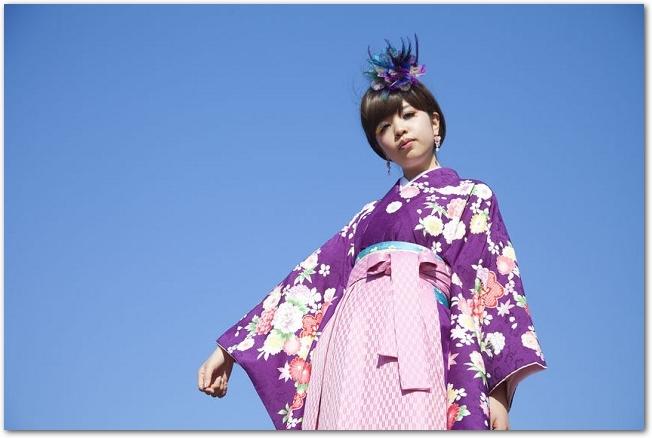 青空を背景に立つ袴姿の女子大生の様子
