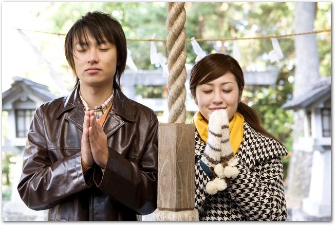 神社に参拝しているカップルの様子