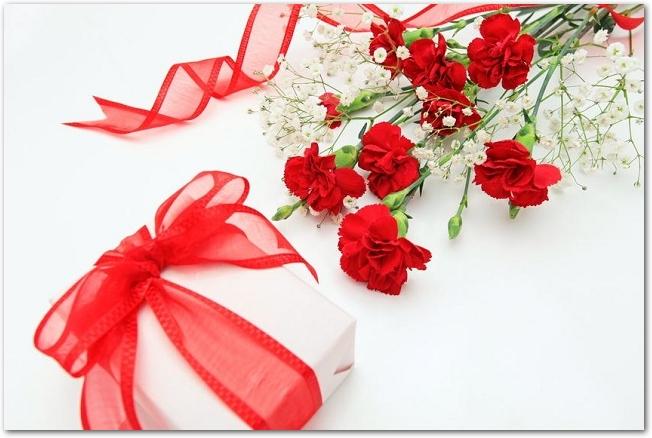 赤いカーネーションとリボンのかけられたプレゼント
