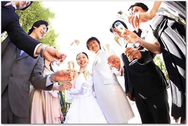 結婚式で友人たちと乾杯する新郎新婦の様子