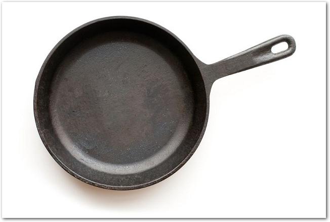 白背景に置かれた鉄製の黒いフライパン
