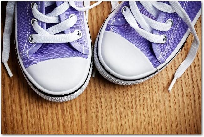 木製の床に置かれた紫色のスニーカーのつま先部分