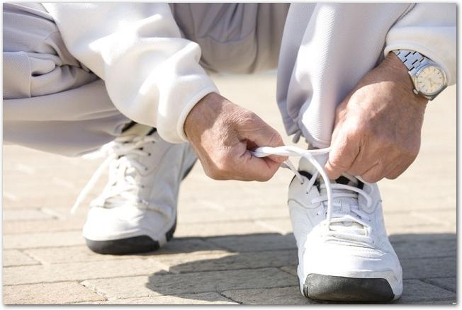 靴ひもを締め直しているシニア男性の足元の様子