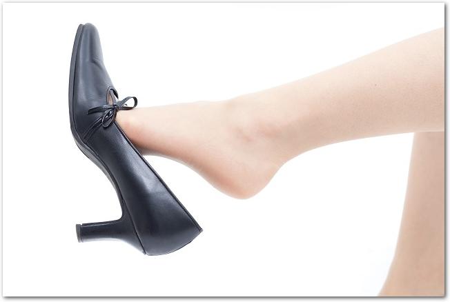 黒いパンプスをつま先でひっかけて持ち上げている足元の様子
