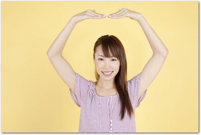 両腕で大きく丸を作る女性の様子