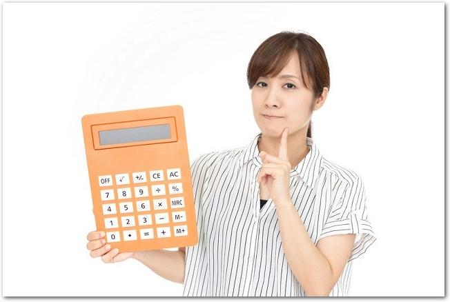 大きなオレンジ色の電卓を持って首をかしげる女性