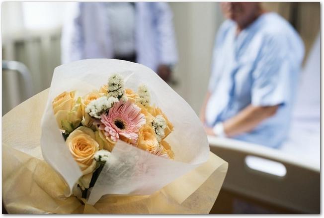 病室に花束を持ってお見舞いに来た様子