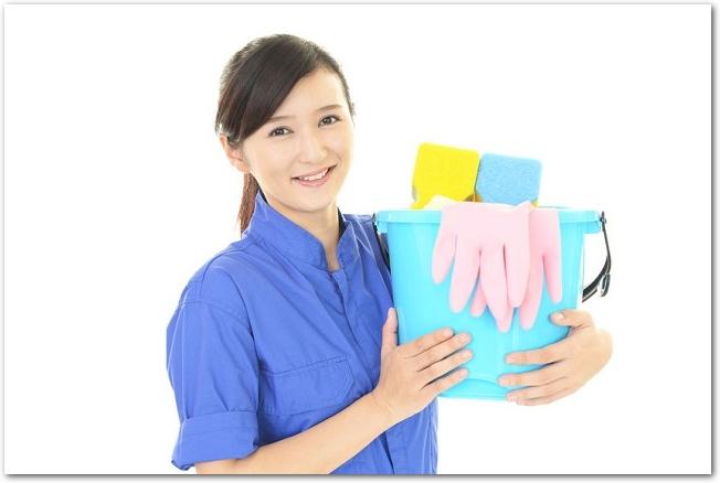 バケツに入った掃除用具を持つ女性の様子