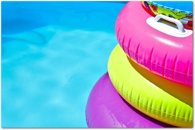 プールに重ねて置かれているカラフルな浮き輪
