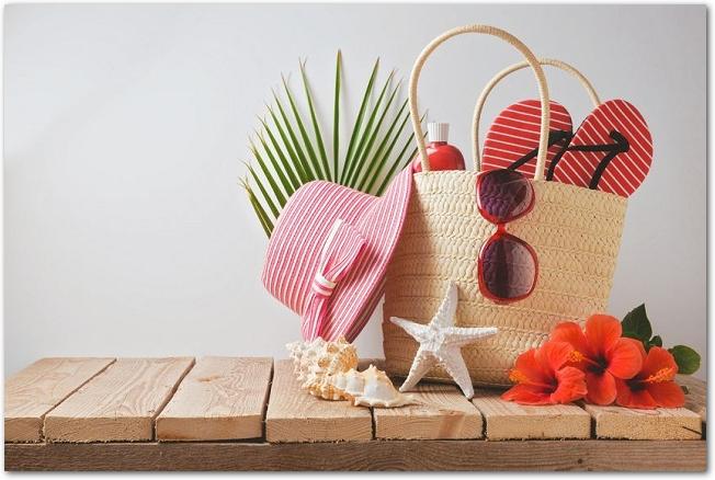 ハイビスカスの花とカゴバッグに入ったビーチグッズ