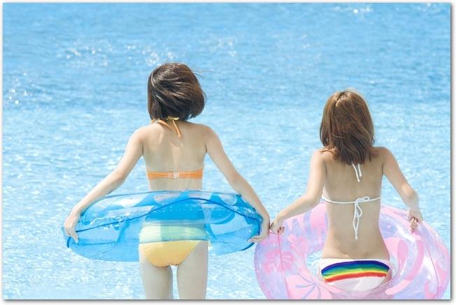 浮き輪をつけた水着姿の2人の女性の後ろ姿