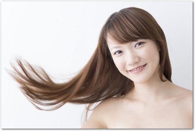 長い髪をなびかせる笑顔の女性の様子